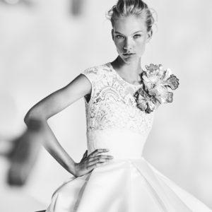 A Jesus Peiro eskuvoi ruha kollekcio 917.sz. image fotoja. A kozeli foton a menyasszonyi ruha csipke felsoresze latszik viraggal diszitve