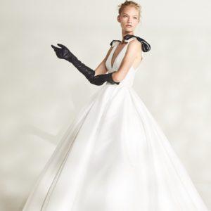 Mély kivágású vállpántos, nagyszoknyás mikadó menyasszonyi ruha. Különlegessége a rejtett zseb, illetve a széles övrész. Image foto