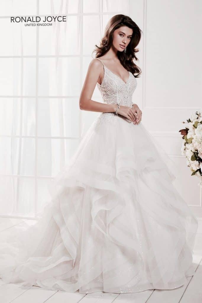 Romantikus, elegáns, vízfodros menyasszonyi ruha csillogó tüll szoknyával. Különlegessége a gyöngyökkel hímzett, vékony pántos body. Style:Carola/69472aRonald Joyce 2020évi kollekciójából.image