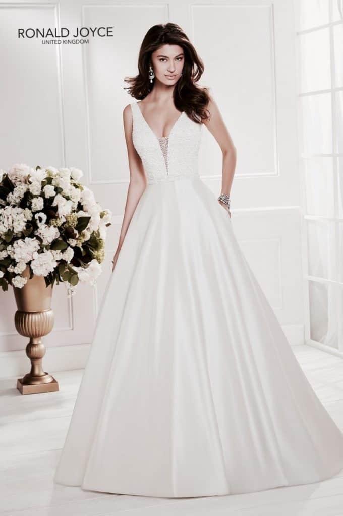 A-vonalú hercegnő stílusú esküvői ruha tüll és szatén kombinálásával. A luxus érzetét a sűrűn gyöngyözött, vállpánotos, V-kivágású body biztosítja. Cora/69466 a Ronald Joyce 2020 évi menyasszonyi ruha kollekcióból.Image fotó