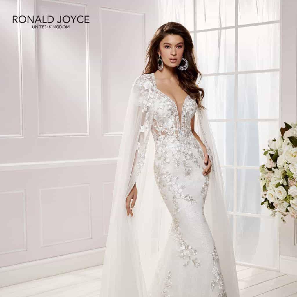 Különleges, elegáns, luxus esküvői ruha a Ronald Joyce 2020 évi kollekciójából. Rövid ujjú sellőruha hosszú fátyolszerű uszállyal. Modell: Clara/69454