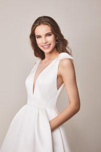 Elegáns szatén haute couture stílusban készült ujjatlan esküvői ruha mély V kivágással, a vállpántján masni díszítéssel valamint rejtett zsebekkel. Kollekció Jesus Peiro 2020, Style: 107. Közelről fotózva