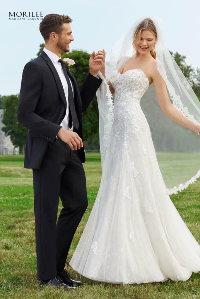 A-vonalú , a test vonalát lágyan követő finom, könnyed net anyagból készült esküvői ruha elegáns csipke hímzéssel, szív alakú nyakkivágással a Morilee 2020 tavaszi, Reverie Signature kollekcióból. Image fotó