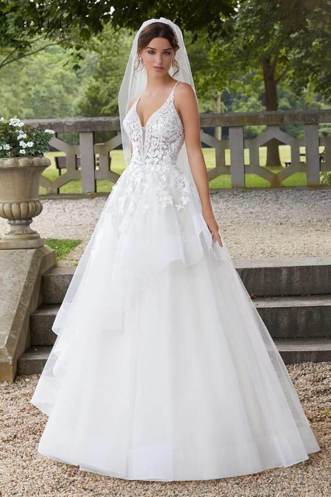 Hercegnő stílusú modell asszimetrikus, fodros kristálytüll szoknyával, vállpántos csipkebodyval. Az esküvői ruha különlegessége a háton lévő keresztpánt. Elölről fotózva