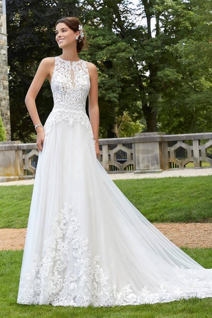 Elegáns, lágyan omló, A vonalú, magasan záródó esküvői ruha különleges csipkszegélyű uszállyal és illúzió részletekkel díszítve. Style: Shani/5806 a Morilee 2021 évi előkollekciójából. Image