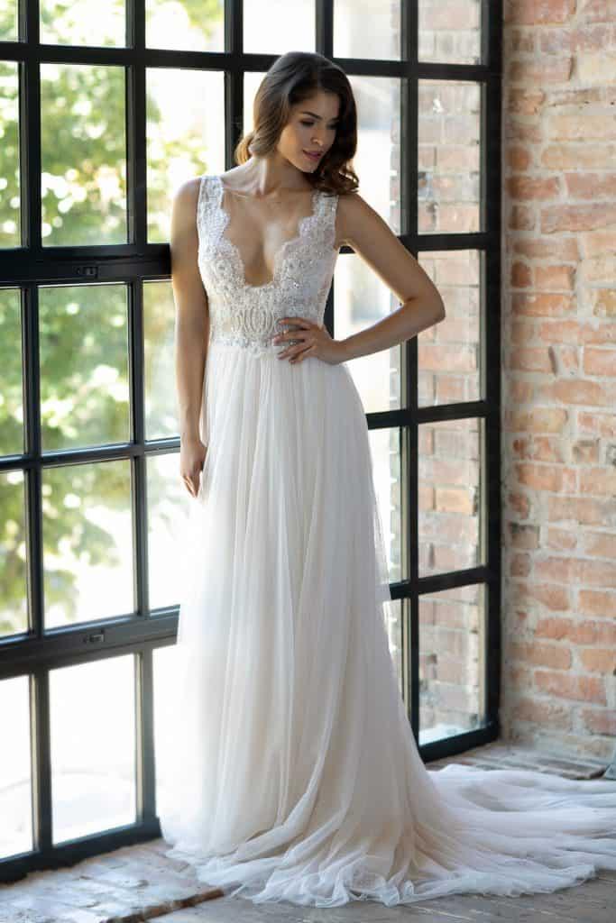 A vonalú romantikus esküvői ruha áttetsző csipkéből széles csipke vállpántokkal és mély dekoltázzsal a Higar Novias divatháztól. Style: Oceano. Modell: Csonka Rebeka /Magyarország szépe 2019, második udvarhölgy/