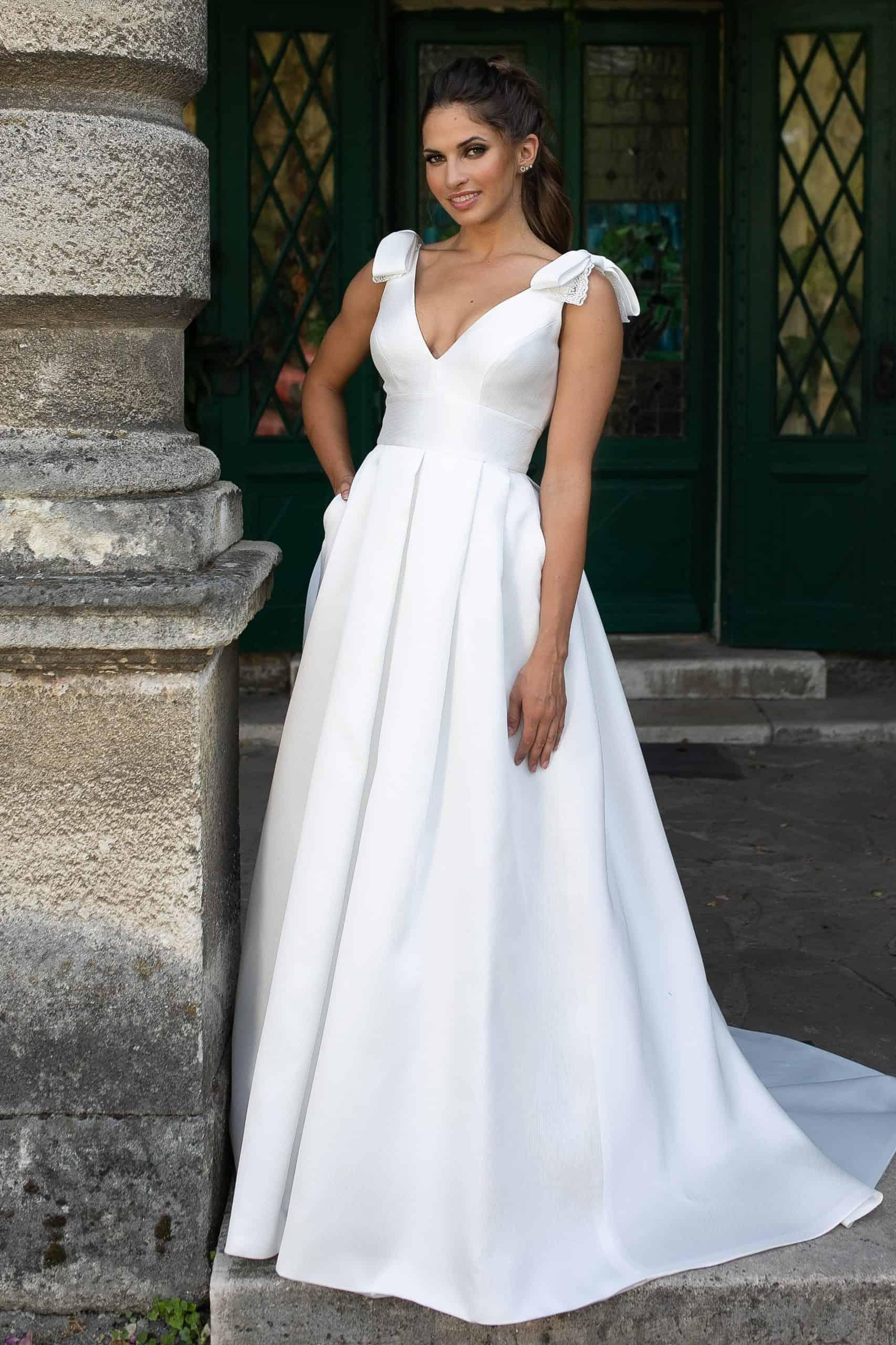 Klasszikus vonalú, hercegnő stílusú szatén menyasszonyi ruha V-nyakkal és mély hátkivágással. Különlegessége a széles szatén öv, bájos masnik a vállon és a szoknya rejtett zsebei. Style: Manu Garcia, Oasis Image fotó