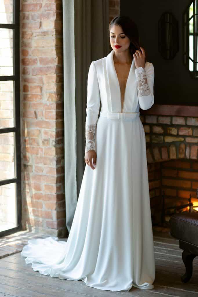 Hosszú ujjú,időtlenül elegáns, trendi esküvői ruha álomszerű részletekkel melyek visszatükrözik viselőjének a személyiségét. Gyönyörű, mély V kivágású, ujjas felsőrész egyedi csipkével díszített illúzió hátmegoldással és magasan sliccelt szoknyával a Higar Novias divatház Manu Garcia kollekciójából. Style: Prince. Modell: Csonka Rebeka /Magyarország Szépe 2019 - második udvarhölgy/