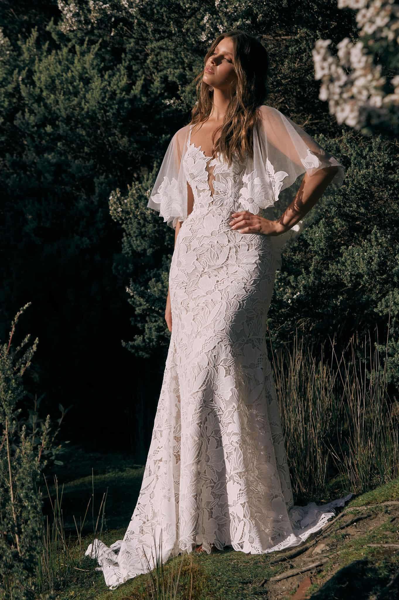 Extavagáns, bohó stílusú, rusztikus csipkéből készült sellő fazonú menyasszonyi ruha szabadtéri, vintage esküvőköz. Elölről fotózva